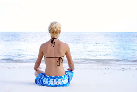 A young girl is meditating on the beach. photo
