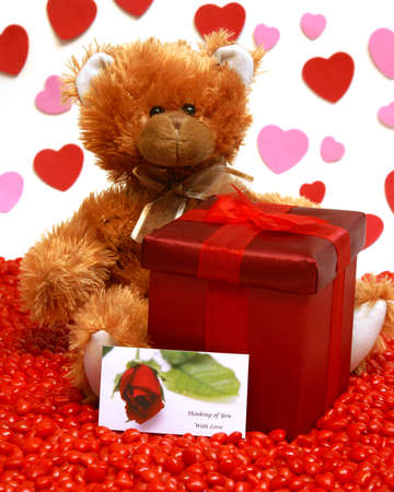 A red gift box and teddy bear to send to someone with love. photo