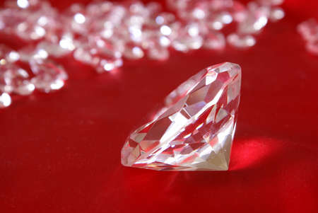 focal point: Many loose diamonds with a focal point on a single one up close over a red satin background. Stock Photo