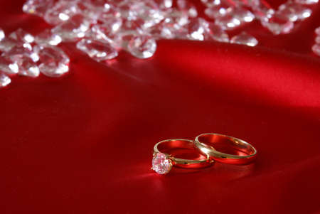 A couple of gold engagement rings with loose diamonds in the background for the symbol of wedded bliss. photo