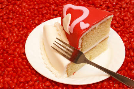 A slice of cake surrounded by candy hearts. photo