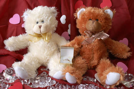 Two teddy bears with an engagement ring surrounded by loose diamonds and heart shapes from a romantic propsal. photo