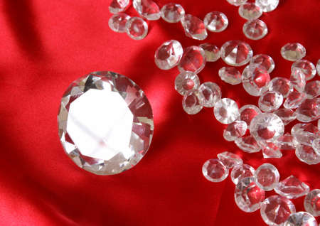 A variety of clear sparkling diamonds on a red satin background. photo
