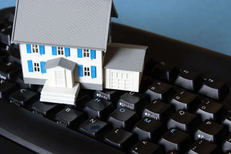 A miniature house with the word home spelt on the keyboard for many conceptual meanings. photo