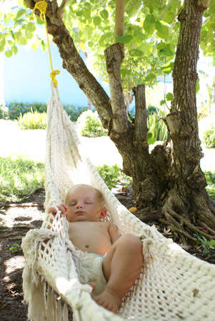 An adorable baby boy sleeps outside in a hammock while dreaming sweetly. photo