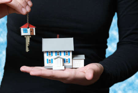 real estate investment: A conceptual image of someone receiving their key to their new home. Stock Photo