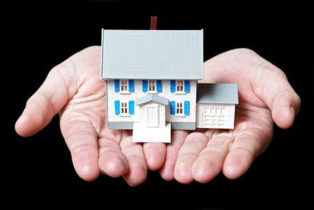 An isolated pair of womans hands holds a toy house. photo