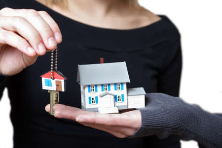 A conceptual image of someone receiving their key to their new home. Imagens