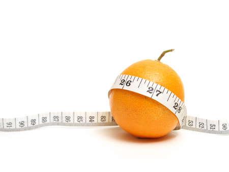 허리의 잘룩 한 선: A ripe citrus fruit with a mesuring tape to represent a fit waistline from healthy eating. 스톡 사진