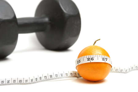 A ripe citrus fruit with a measuring tape and a barbell in the background to conceptualize on fitness. photo