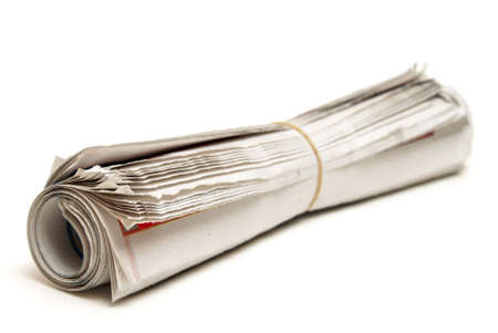 An isolated newspaper that has been rolled and banded.