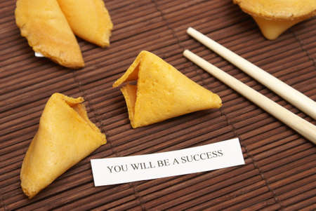 stating: A low contrast still life image of a fortune cookie with a message stating that you will be a success. Stock Photo
