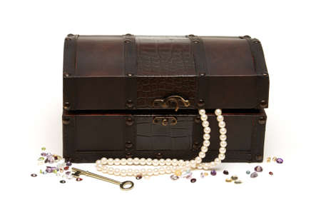 An isolated treasure chest with some loose gemstones and a pearl necklace around it. photo