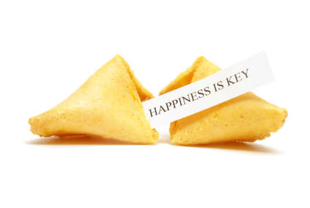 A cracked open fortune cookie stating that happiness is key. photo