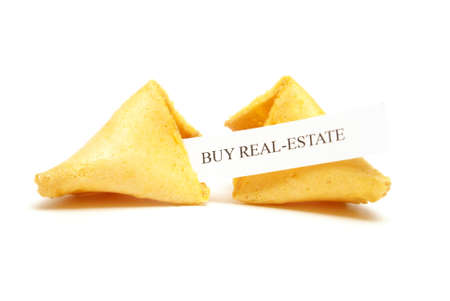 stating: A cracked open fortune cookie stating to buy real estate. Stock Photo