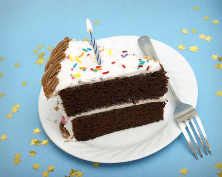 layer cake: A slice of chocolate cake with a single lit candle. Stock Photo