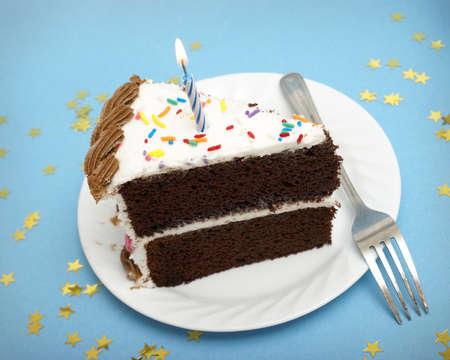 trozo de pastel: Una rebanada de pastel de chocolate con una sola vela encendida.