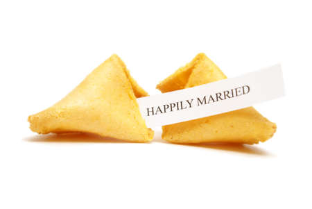 A cracked open fortune cookie saying happily married. photo
