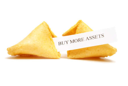 A cracked open fortune cookie stating to buy more assets. Stock Photo - 9779403