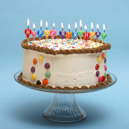 A cake and its candles that read happy birthday.