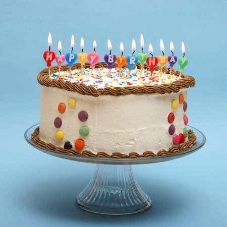 pastel aniversario: Un pastel y velas es que leen feliz cumpleaños.