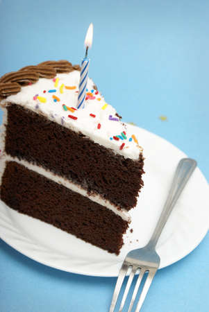 candle: A slice of chocolate cake with a single lit candle. Stock Photo