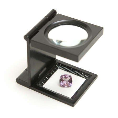 appraise: A loupe inspection of a finely cut amethyst gemstone to understand its value.