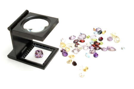magnification: A loupe with various cut gemstones for the jeweler to inspect their quality and value.