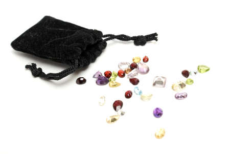 A handfull of mixed genuine gemstones isolated on white that have been spilled out from the pouch. photo