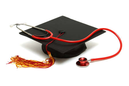 stethoscope: An isolated mortarboard and stethoscope to conceptualize the medical graduate. Stock Photo