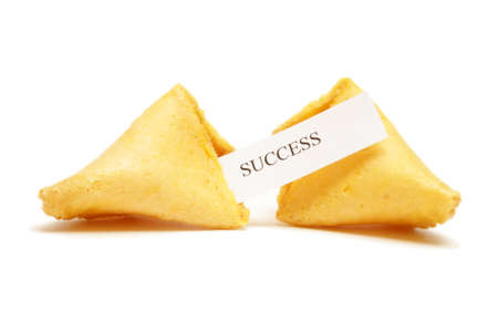 A cracked open fortune cookie stating the word success. photo