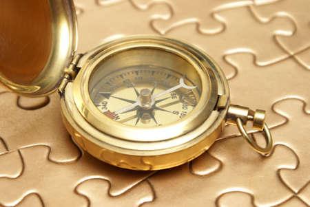 異なった概念のための黄金のジグソー パズルの上に真鍮コンパス残り。 写真素材