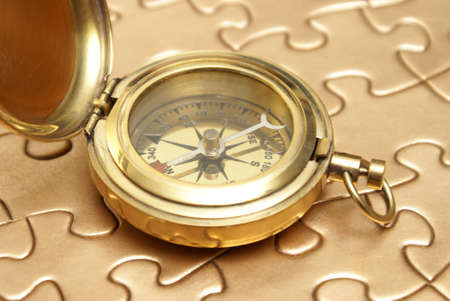 A brass compass rest on top of a golden jigsaw puzzle for different concepts.