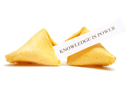 A cracked open fortune cookie stating that knowledge is power. photo