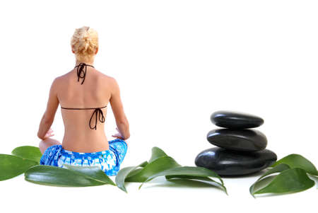 A young woman meditates among some large leaves and balanced rocks.