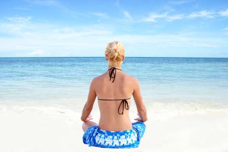 A young woman meditates along the shores of the tropical ocean.