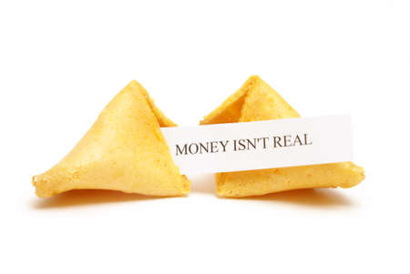 A cracked open fortune cookie stating that money isnt real. photo
