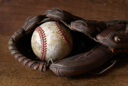 A low contrast image of a well used hardball and glove for those who love the sport of baseball. Stock Photo - 9909969