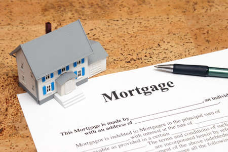 loans: A conceptual image of a scale house and mortgage forms for the people buying a house.