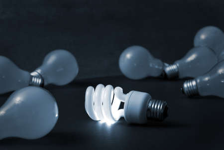 A new energy efficient CFL light bulb shines while the old ones fade into darkness.