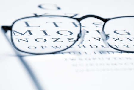 An eye chart with a pair of glasses and selective focus within the frames to emphasize vision correction. photo
