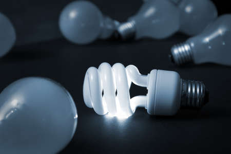 energy saving: A new energy efficient CFL light bulb shines while the old ones fade into darkness.