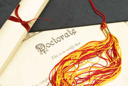 doctorate: A closeup shot of a doctorate and diploma scroll with the tassels of a mortar board. Stock Photo
