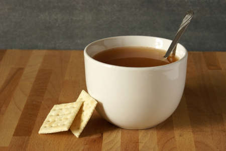 soup spoon: A bowl of soup and some soda crackers leaning on it.