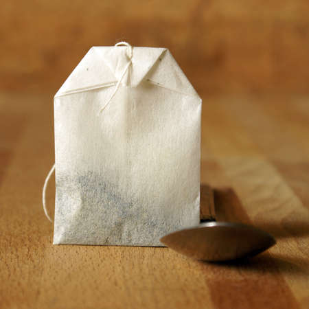 A square format shot of a tea bag and spoon for preparing the beverage.