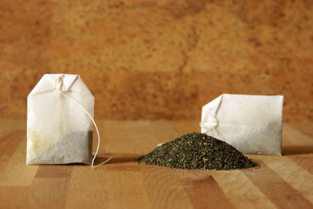 A couple of bags are next to a pile of green tea leaves. photo