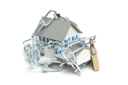 residential building insurance: A house is wrapped with a chain and padlock to represent home security concepts. Stock Photo