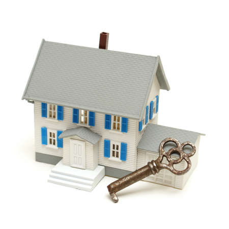 A house and a skeleton key represent home security concepts. photo