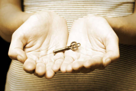 A woman openly holds her hands with an antique skeleton key. Imagens