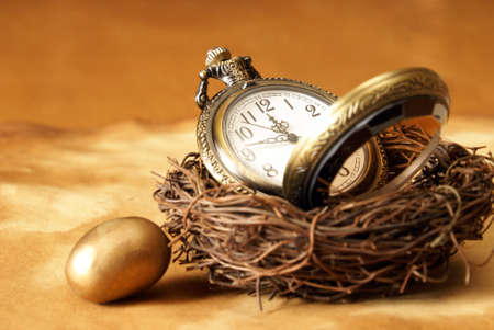 A conceptual image of a pocket watch inside a birds nest with a golden egg resting outside.